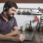 uomo che guarda video al computer con cuffie in cucina